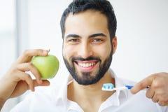 Man Eating Apple. Beautiful Girl With White Teeth Biting Apple. High Resolution Image stock image