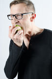 Man eating apple. Man eating green apple -biting royalty free stock photo