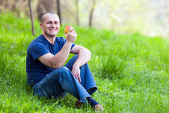 Man eating an apple outdoor Royalty Free Stock Images