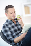 Man eating apple while reading Royalty Free Stock Image