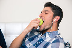 Man eating apple on the sofa Royalty Free Stock Image