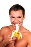 Man eating banana. Young handsome man eating banana royalty free stock photography