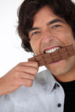 Man eating a bar of chocolate Stock Photo