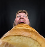 Man eating a big bread. Closeup of a man eating a huge bread over black Royalty Free Stock Images