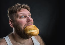 Man eating a big bread. Side view of a man eating a big bread over black Stock Images