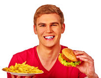 Man eating big sandwich and fried potatoes. Royalty Free Stock Images