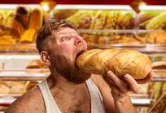 Man eating bread in the shop. Closeup of a man eating bread in the bakery shop Royalty Free Stock Image