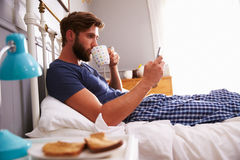 Man Eating Breakfast In Bed Whilst Using Mobile Phone Stock Photography