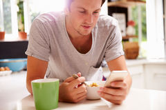 Man Eating Breakfast Whilst Checking Mobile Phone Stock Photos