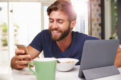 Man Eating Breakfast Whilst Using Digital Tablet And Phone Stock Photo