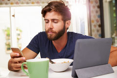 Man Eating Breakfast Whilst Using Digital Tablet And Phone Royalty Free Stock Photography