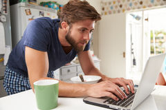 Man Eating Breakfast Whilst Using Mobile Phone And Laptop Stock Photo
