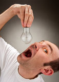Man eating bulb. Absorption ideas. Man trying to eat electrical bulb stock photos