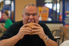 Man eating burger in fast food restaurant Stock Image