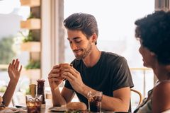 Man eating burger with friends at restaurant. Young men eating burger while sitting with female friends at a restaurant. Man hanging out at cafe with friends and stock photos