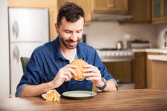 Man eating a burger at home Stock Images