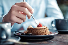 Man eating cake with strawberries in cafe, close-up Royalty Free Stock Image
