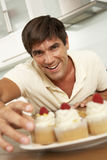 Man Eating Cakes In Kitchen Stock Photography
