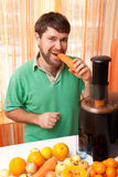 Man eating a carrot and makes juice Stock Images