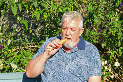 Man eating a carrot. stock photography