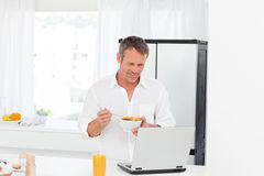 Man eating cereal while he is working Stock Photography