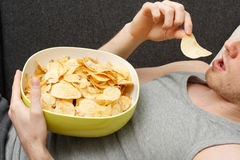 Man eating chips Stock Photography