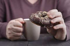 Man eating chocolate donut Stock Images