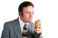 Man Eating Chocolate Ice Cream Cone. Man in business suit eating a chocolate ice cream waffle cone. Isolated on white background stock photography