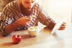 Man eating corn flakes and milk with digital tablet Royalty Free Stock Photography