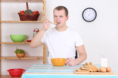 Man eating corn flakes with milk in his kitchen Stock Images