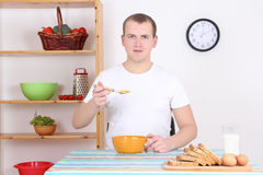 Man eating corn flakes with milk in the kitchen Stock Photos