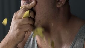 Man eating crisps with appetite, psychological problem, unhealthy food addiction. Stock footage stock video footage