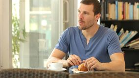 Man eating a croissant in a coffee shop. Man having breakfast eating a croissant and drinking coffee in a restaurant or home stock video
