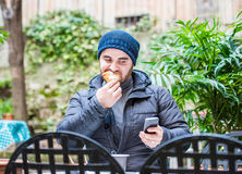 Man eating a croissant and looking at his smartphone in a garden Royalty Free Stock Images