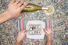 Man eating dollars as a servant pours champagne. Man eating dollar bills as a servant pours champagne from a bottle overhead on a background of money in a Stock Images