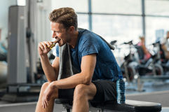 Man eating energy bar. Sweaty young man eating energy bar at gym. Handsome mid guy enjoying chocolate after a heavy workout in fitness studio. Fit man biting a royalty free stock photos