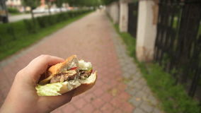 A man is eating fast food on the street, bearing in hand a hamburger. stock footage