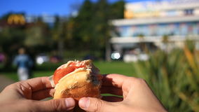 A man is eating fast food on the street. He wears a hamburger and eats it. Against the background of a blurry city stock video