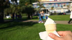 A man is eating fast food on the street. He wears ice cream and eats it. Against the background of a blurry city street stock video footage