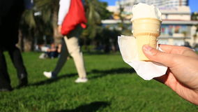 A man is eating fast food on the street. He wears ice cream and eats it. Against the background of a blurry city street stock video