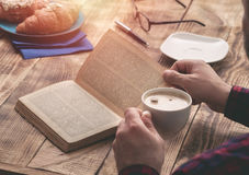 Man eating french breakfast and reading book royalty free stock photo