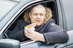 Man eating french fries in the car. In winter day Stock Photos
