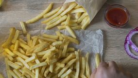 Man eating french fries potato with ketchup, unhealthy fast food addiction. Stock footage stock video