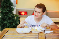 Man eating French fries and smiling. Happy, road, fast food Royalty Free Stock Photography