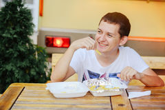 Man eating French fries and smiling. Happy, road, fast food Stock Images