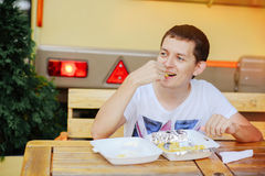 Man eating French fries and smiling. Happy, road, fast food Royalty Free Stock Photo