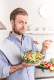 Man eating fresh vegetable salad in the kitchen Royalty Free Stock Photo