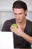 Man eating a green apple Stock Photos