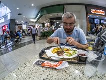 Man eating hambúrguer, potato, and salad at the food court in a mall in Sao Paulo city