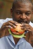 Man eating hamburger. African american man eating a hamburger Stock Photos